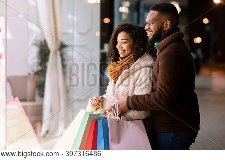 Happy Loving Family. Smiling African American Man Embracing His Woman, Couple Looking At Shop Window
