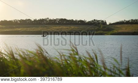 A Man Rides A Motor Boat In An Inflatable Boat On A Lake At Sunset. Fisherman Rides A Motor Boat On