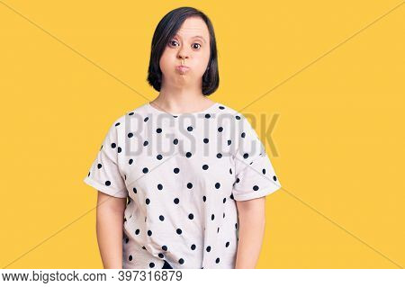 Brunette woman with down syndrome wearing casual clothes puffing cheeks with funny face. mouth inflated with air, crazy expression.