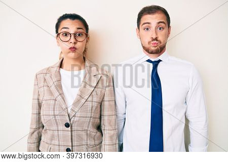 Beautiful couple wearing business clothes puffing cheeks with funny face. mouth inflated with air, crazy expression.