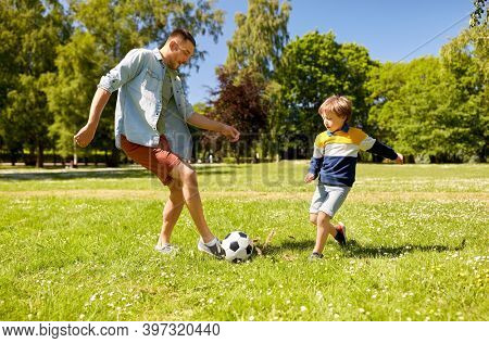 family, fatherhood and people concept - happy father and little son with ball playing soccer at summer park