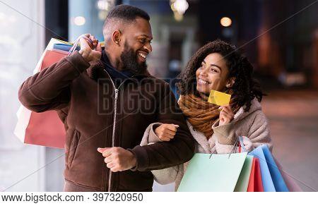 Lets Buy Something. Portrait Of Smiling Black Woman Showing Debit Credit Card To Man, Holding Shoppi
