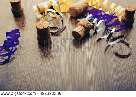 Champagne Corks And Christmas Ribbons On A Wooden Table