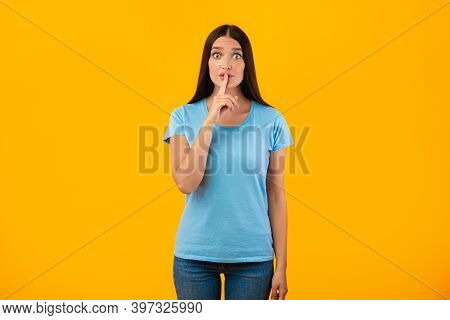 Shh, Keep Silence. Portrait Of Funny Lady Gesturing Hush Sign Posing Isolated Over Studio Yellow Bac