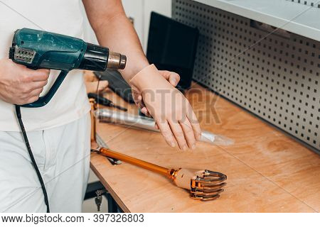 Worker S Hands Drying A Part Of An Artificial Limb Glow With A Blow Dryer.