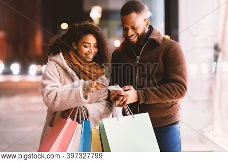 Shopping Together Concept. Portrait Of Two Happy African American Customers Using Smartphone, Woman