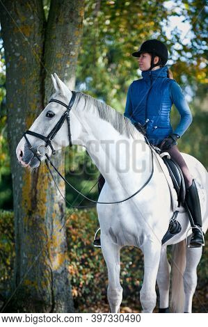 Equestrian Lady Riding White Horseback In Autumn Alley. Vibrant Colored Outdoors Vertical Fall Seaso