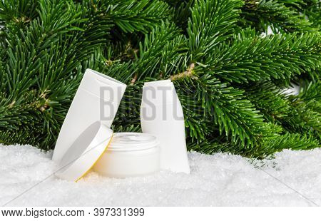 Set Of White Winter Skin Care Cosmetic Products In Snow With Christmas Tree Branches. Open Face Crea