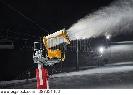 Snow canon making artificial snow on a skiing slope at night, preparing for skiing season