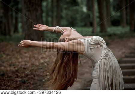 Beautiful Young Woman With Long Hair Dancing In Nature.