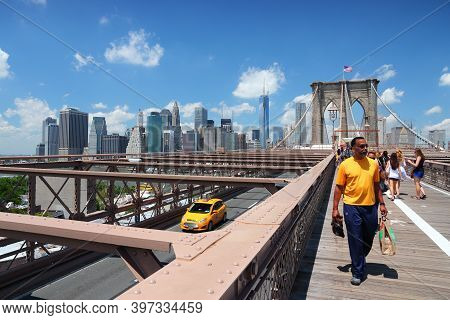 New York, Usa - July 5, 2013: People Walk Along Famous Brooklyn Bridge In New York. Almost 19 Millio