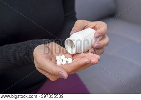 A Woman Spilling Out White The Pills From A Bottle Container To Her Hand. A Woman Pouring Pills From
