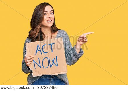 Young brunette woman holding act now banner smiling happy pointing with hand and finger to the side