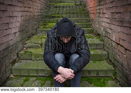 A Drug Addict Man Is Sitting On The Street, Experiencing A Drug Addiction Crisis. Social Problems