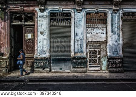 Havana, Cuba, July 2019, Woman Walking In Front Of A Dilapitated Building With The Closed Cafeteria
