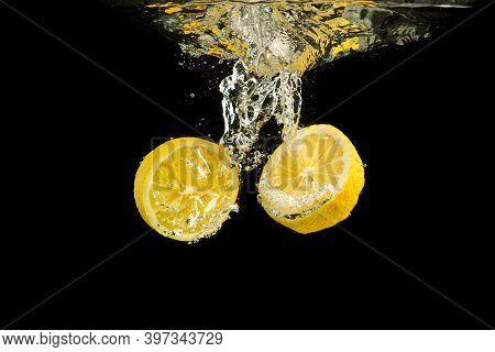Fresh Yellow Lemon Halves In Water Splashing Isolated On Black Background.refreshment Concept