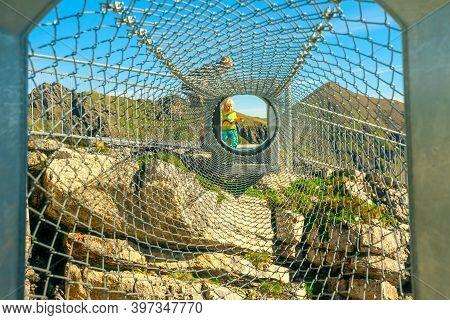 Birg, Murren, Switzerland - Aug 19, 2020: Child Walks The Tube Made Of Nets Of Thrill Walk On Schilt