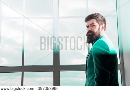 Modern Life. Business Man Standing At Window With Cityscape. Brutal Bearded Man. Mature Hipster With