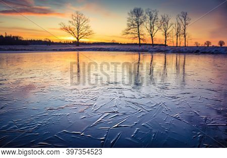 A Beautiful Frozen Pond In The Rural Scene During The Morning Golden Hour. A Winter Scenery Of North