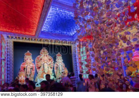 Blurred Image Of Devotees Gathered To Pray To Goddess Durga During Durga Puja Festival At Night. Sho