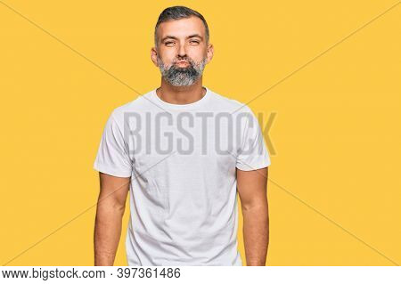 Middle age handsome man wearing casual white tshirt puffing cheeks with funny face. mouth inflated with air, crazy expression.