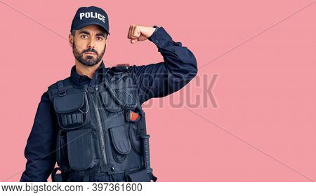 Young hispanic man wearing police uniform strong person showing arm muscle, confident and proud of power