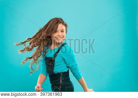 Enjoying Her Favorite Hairstyle. Adorable Girl With Curly Hairstyle Waving On Blue Background. Small