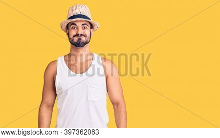 Young hispanic man wearing casual summer hat puffing cheeks with funny face. mouth inflated with air, crazy expression.