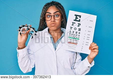 Young african american optician woman with braids holding optometry glasses and medical exam puffing cheeks with funny face. mouth inflated with air, catching air.