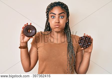 Young african american woman with braids holding chocolate donut and waffle puffing cheeks with funny face. mouth inflated with air, catching air.