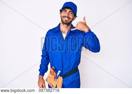 Handsome young man with curly hair and bear weaing handyman uniform smiling doing phone gesture with hand and fingers like talking on the telephone. communicating concepts.