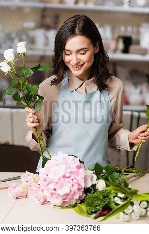 Female Florist With Roses Looking At Flowers On Desk, While Composing Bouquet On Blurred Background