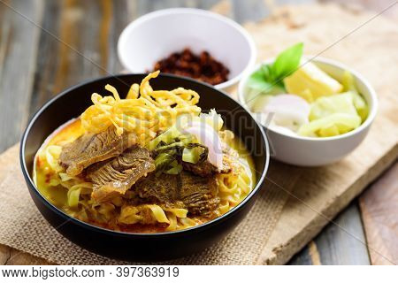 Northern Thai Food (khao Soi), Spicy Curry Noodles Soup With Beef In A Bowl Eating With Crispy Deep-