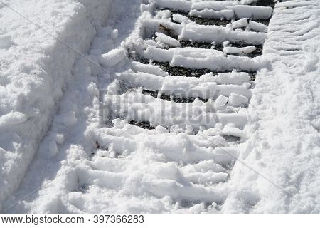 Tire Tracks In The Snow At The Parking Area