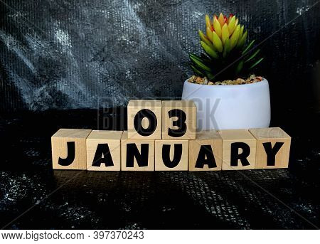 January 3 On A Black Background On Wooden Cubes .next To It Is A Pot With A Flower .calendar For Jan