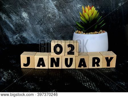 January 2 On A Black Background On Wooden Cubes .next To It Is A Pot With A Flower .calendar For Jan