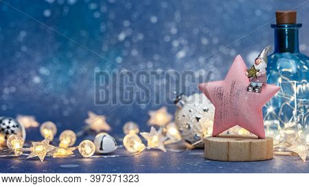 Christmas Background With Noel Gnome Sitting On Wooden Star Against Blurred Blue Background With Glo