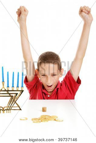Little boy playing with his dreidel on Hanukkah.   White background.