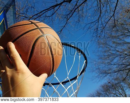 Hand Dunking A Basketball With Hoop And Trees