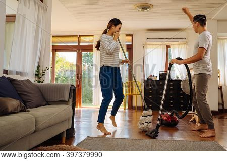 Happy Young Couple Of Woman Dancing And Singing While Cleaning With Vacuum Cleaner Machine And Man M