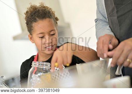 Portrait of cute 10-year-old african-american girl making cookies