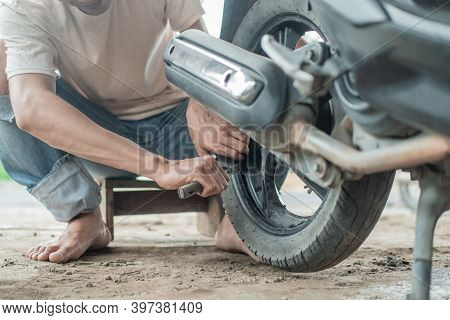 Tire Repairman Uses A Tire Scraping Tool To Remove Motorcycle Tires