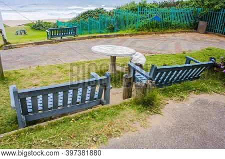 Green Benches On A Slope Overlooking The Sea