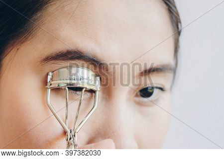 Closeup Of Young Asian Woman Using Eyelash Curler. Eyelash Curler Is A Hand-operated Mechanical Devi