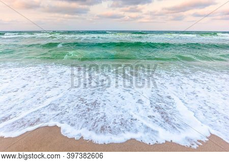 Golden Cloudy Sunset Above The Green Sea Waters. Waves Crashing The Sandy Beach. Clear Horizon. Chan