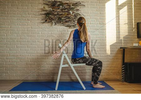 Woman Doing Yoga At Home. Blue Mat And Undershirt. Twisting Pose With A Chair, Sunny Day. Natural Pa
