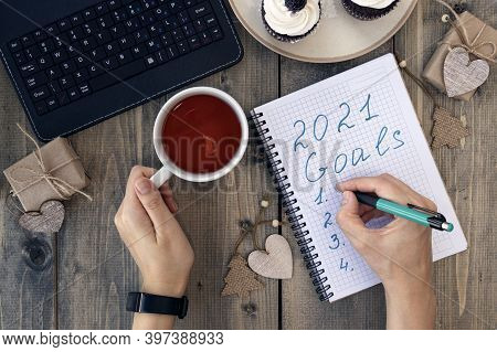 Womens Hands Write In A Notebook New Years Goals On A Wooden Table Over With Christmas Gifts And Cup