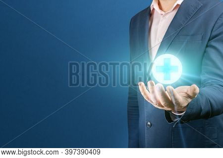 Businessman Hand Holding Medicine Sign. Man Holds A Glowing Medical Cross Sign In His Hand. Concept