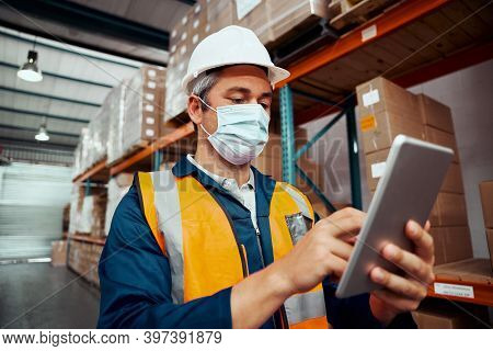 Male Factory Worker Using Digital Tablet Wearing Protective Mask At Warehouse
