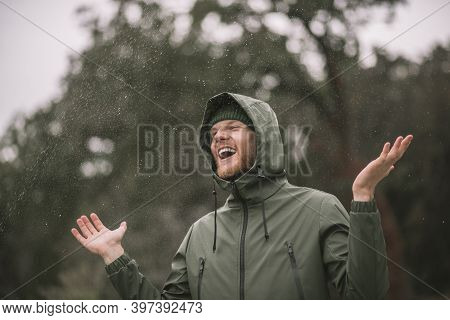 Young Man In A Green Coat Standing In The Rain And Smiling